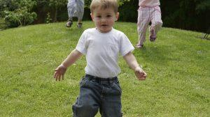 Little boy running down a grassy hill.
